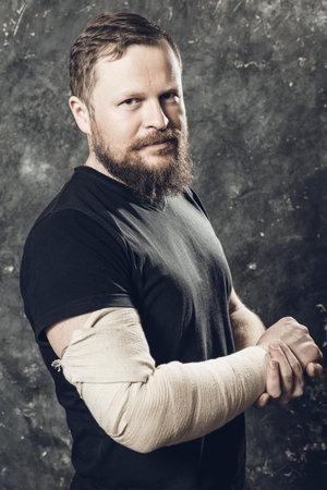 Matured man with bandaged hand studio portrait. Reklamní fotografie