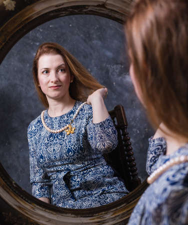 Cheerful middle aged woman looks in vintage style mirror