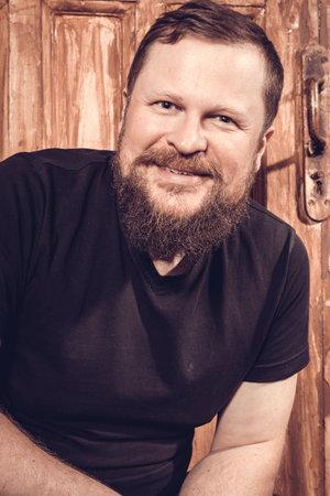 Mature bearded man sitting on vintage door background