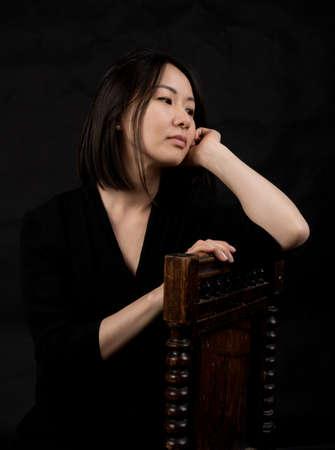 Beautiful korean woman dressed in black dress sitting on chair studio portrait.
