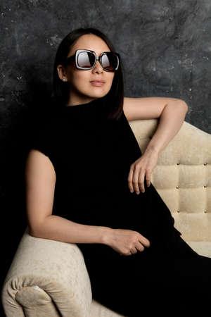 Beautiful korean woman dressed in black dress sitting on sofa