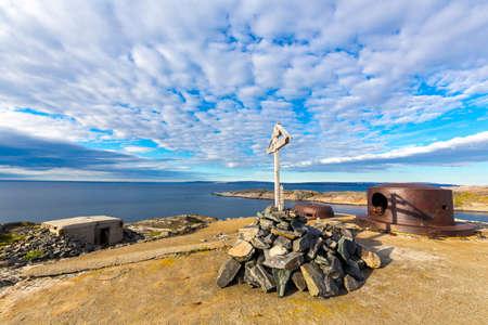 Military bunker of ww2 on Barents sea shoreline and christian cross Stock fotó