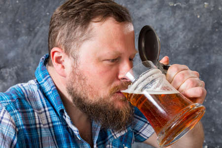Matured smiling bearded man in shirt with beer mug