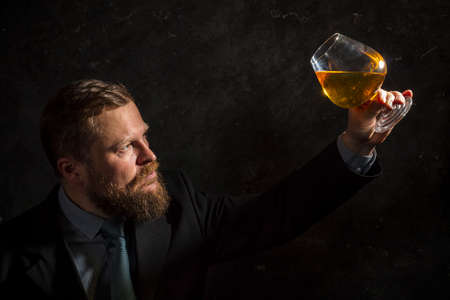 Solid confident bearded man in suit with glass of whisky