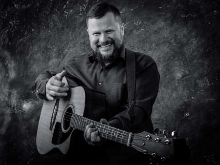 Mature musician plays acoustic guitar emotional studio portrait.