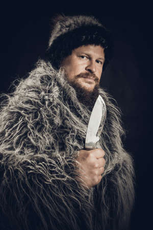 Bearded hunter dressed in a fur mantle and fur hat with knife