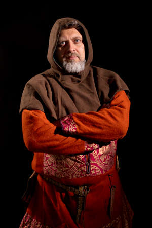 Mature bearded man in traditional medieval historic clothes studio portrait.