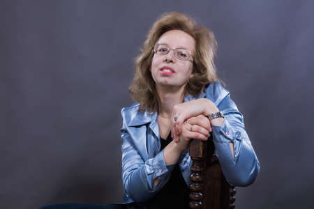 Cheerful 40 years old woman dressed in blue jeans and azure jacket