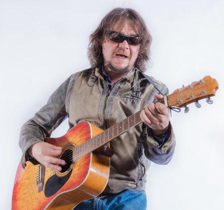 Mature musician plays acoustic guitar studio portrait. Reklamní fotografie