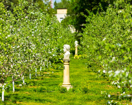Beautiful spring garden alley view with Pushkin statue