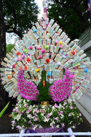 formalize: Money decorate is peacock at a buddhist temple in Thailand where financial donations are placed in order to receive merit and good fortune Stock Photo