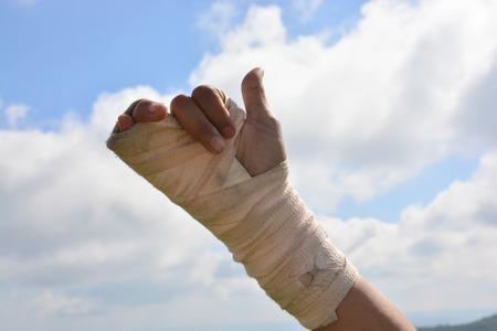 splint: las personas con dolor en la muñeca en un ejercicio vendaje elástico dedos con el fondo del cielo