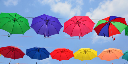 Colorful umbrellas background. Coloruful umbrellas urban street decoration. Hanging Multicoloured umbrellas over blue sky. Stock Photo