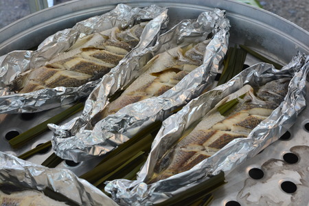 steamed fish with lemongrass & herbs on aluminum foil cooking in steaming pot