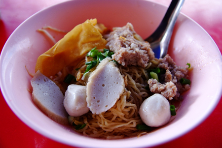Dried egg noodles with fish balls and minced pork, note  select focus with shallow depth of field