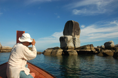 Tourists are taking pictures on the boat at Koh Hin Son.