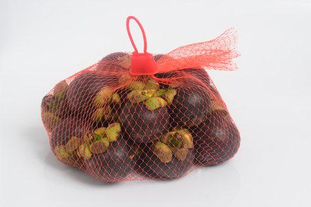 Mangosteen Fruit in Mesh bag 1 kilo white background, famous fruit of Thailand