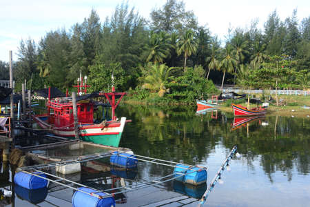 NARATHIWAT, THAILAND – 1 JANUARY 2021 : Local fishing village along the Bang Nara River with kolae boats colorful