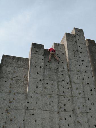 Boy on climbing wall photo