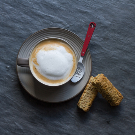 Cappuccino in a cup with teaspoon and rusks Stock Photo