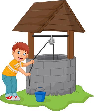 Le garçon prend de l'eau dans le puits