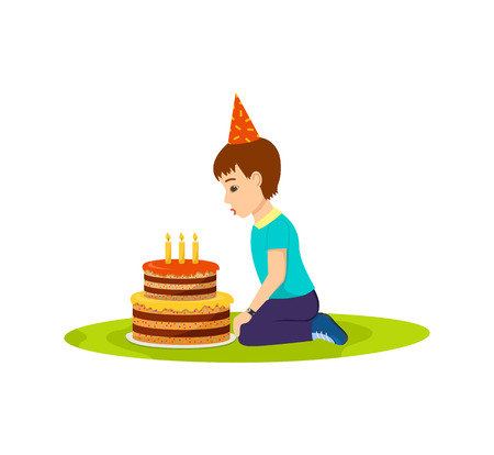 Little boy in a festive mood blows out birthday cake Stock Photo