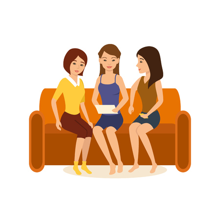 teenagers having fun: Girlfriends are sitting on couch, discussing photos and funny stories.