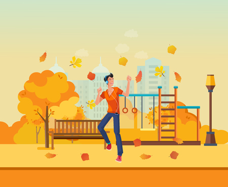 entertaining area: Young man listens to music and dancing in autumn park. Stock Photo