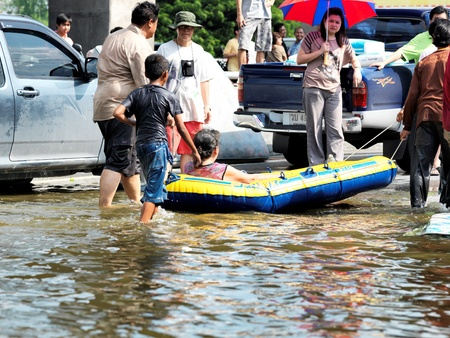 October 21, 2011 Rongsit Road, Phathumtrani, Thailand: Rescue  navigating  a  boat with sick woman through the water during the worst flooding in decades
