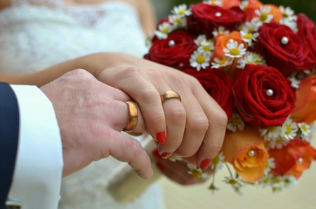 man: Wedding couple holding hands with new rings