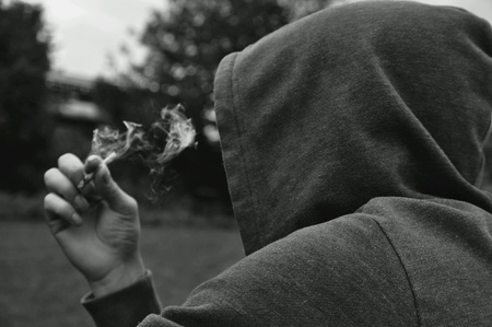 white: Mysterious person wearing a hoodie smoking