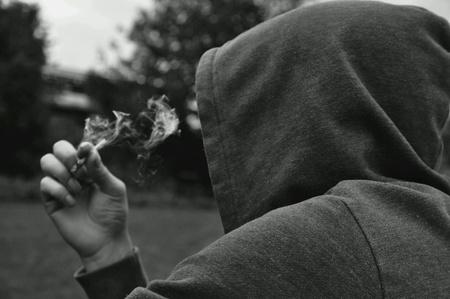 dark: Mysterious person wearing a hoodie smoking