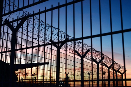 grid: View through a barbed wire fence with beautiful colorful sky in the background located in France Stock Photo