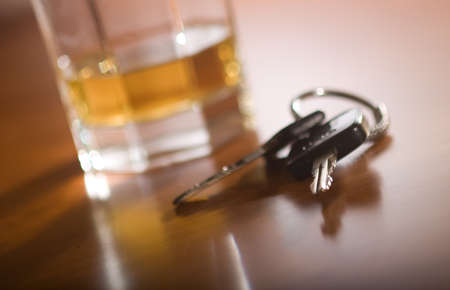 drink and drive: A set of car keys in the foreground and glass of whiskey behind.