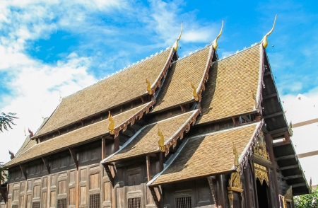 Antique wooden temple in Chiang mai of Thailand with blue sky photo