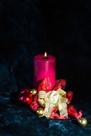christmas candle in red and gold decoration with black velvet background photo