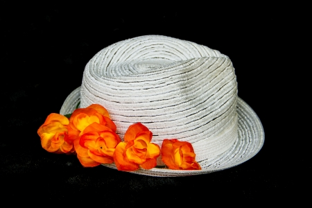 white elegance and  classic hat with orange roses on black background photo
