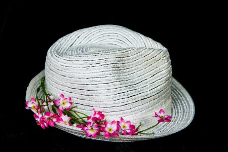 white elegance and  classic hat with pink flowers on black background photo