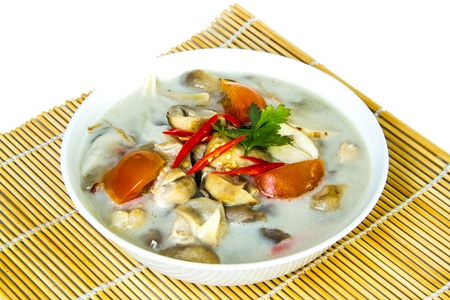 Tom kha of thai food in white bowl on bamboo wrap photo