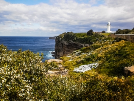Rock cliff and lighthouse beside the sea at Sydney Australia Stock Photo