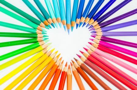 Kleurenpotloden in hartteken op witte bacground Stockfoto