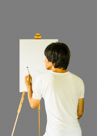 Artist start painting on the canvas which lay on the  tripod paint.