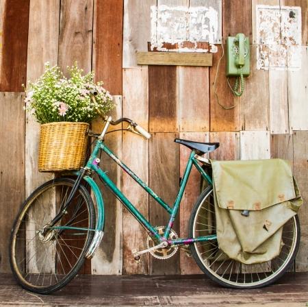 vendimia: bicicleta de la vendimia en la pared de la casa de madera de época