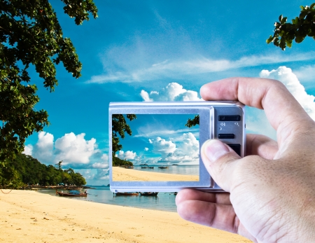 Compact digital camera with view of the beach  photo