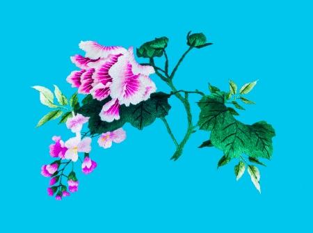 punto cruz: Seda de coser a mano de flores sobre fondo azul
