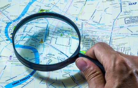 Hand holding magnifying for searching on map. Stock Photo