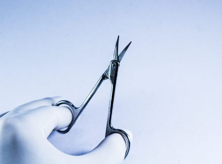 Hand with white glove holding the scissors. photo