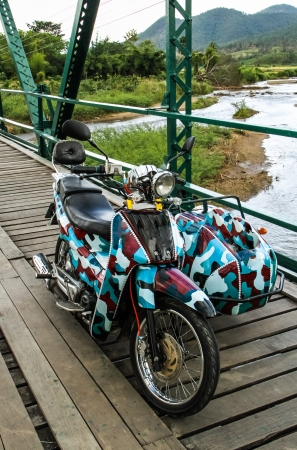 Soilder print motorcycle trailer on the history bridge at Pai,Thailand  photo