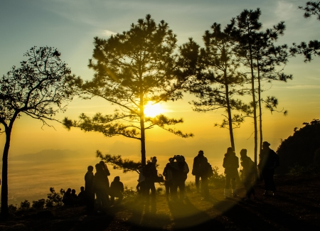 Sunrise on the mountain view with a group of people.
