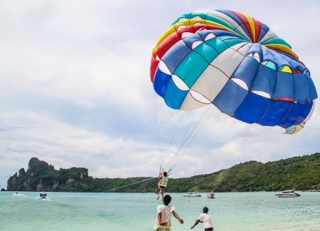 parachuting: Tourist ejoy parachuting in the sea  Stock Photo